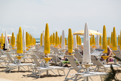 Photo of some bright yellow beach umbrellas and beach loungers