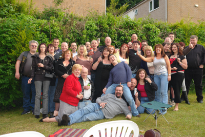 A picture of a couple of dozen people posing for the camera in a garden