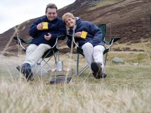 Two people on camping chairs sitting with drinks in front of a disposable barbecue