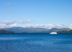 A tour boat cruising Loch Lomond with mountains in the distance