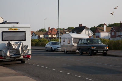 Motorhome, car and caravan all parked by the road.